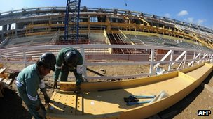 Two construction workers with the unfinished Maracana stadium behind them, 5 May 2012
