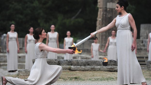 The flame for the London 2012 Olympic Games relay is passed from bowl to torch at the lighting ceremony in Olympia, Greece