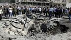 Syrians stands beside a crater created by a blast in Damascus on 10 May 2012