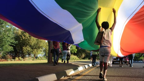 Person walking under a huge rainbow flag