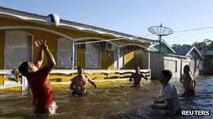 Residents play volleyball in a flooded street in Anama 6 May 2012