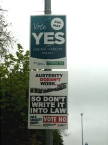 Two posters on a lamppost, one says vote yes, the other says vote no