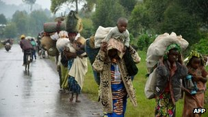 Residents of the town of Kibumba walk on 8 May 2012 on the road to Rutshsuru, some 30km (20 miles) from the eastern Democratic Republic of Congo city of Goma