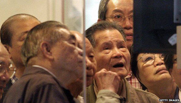 Elderly investors crowd around a share price monitor at a brokerage in Hong Kong