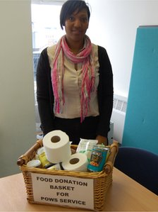 Lynette Oyaide in front of a food donation basket