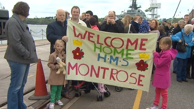 Families holding a welcome poster for the crew of HMS Montrose