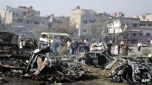 A handout picture released by the Syrian Arab News Agency (Sana) shows onlookers gathering amid the debris and destroyed vehicles at the scene of twin blasts in Damascus on 10 May