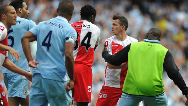 QPR midfielder Joey Barton is led away by Manchester City substitute Micah Richards