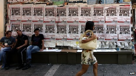 Woman walking past Syriza posters