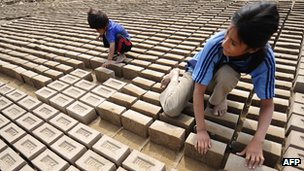 Children turning adobe bricks for drying in Huachipa, some 50 km east of Lima, in 2008