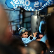 Boy with inflatable trophy at Manchester City parade