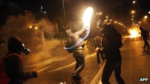 A protestor throws a molotov cocktail at riot police outside the parliament in Athens