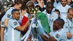 Manchester City players hold the Premier League title