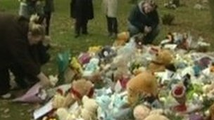 People laying flowers for baby Peter
