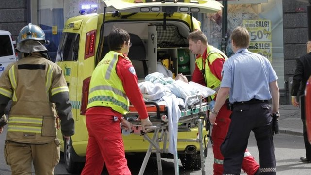 Medical staff load a man, who set himself on fire outside the Oslo courthouse where Anders Breivik is being tried, into an ambulance