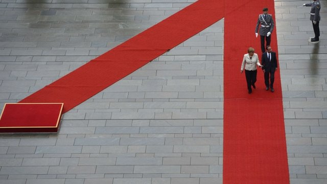 German Chancellor Angela Merkel (L) and the new French president Francois Hollande walk to review a guard of honour in front of the German Chancellery