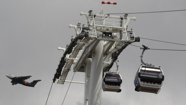 "A plane flies past as Transport for London""s gondola lift cable cars are tested across the River Thames, in London"