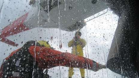 BBC reporter Joe Lumley (yellow) being winched onto the vessel