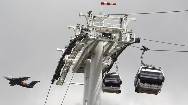 Cable cars suspended on wires with aeroplane flying in the distance