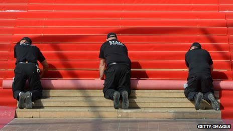 Workers unroll the red carpet in Cannes