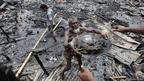 A man salvages his belongings after a fire in a slum at Shyamoli in Dhaka