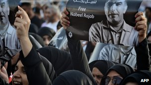 A female demonstrator holding Nabeel Rajab's picture