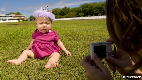 Woman takes a photography of a young child