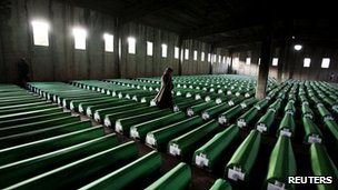 Woman walks past coffins containing the remains of war crimes victims in Potocari, near Srebrenica, on 9 July 2011
