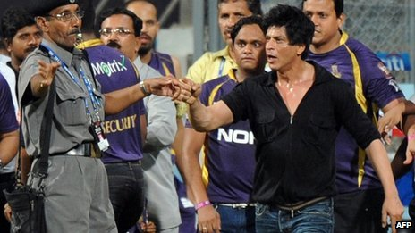 Bollywood actor and Shah Rukh Khan (R) gestures towards a security guard blowing a whistle to direct children accompanying him off the playing field on Wed 16 May night