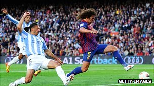 Carles Puyol of FC Barcelona scores the opening goal against Malaga CF in May 2012