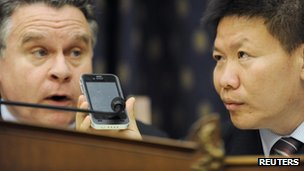 Bob Fu (R) helps U.S. Representative Chris Smith (R-NJ) speak by phone with blind Chinese dissident Chen Guangcheng in the middle of a Congressional-Executive Commission on China hearing on Chen&quot;s case, on Capitol Hill in Washington May 3, 2012.