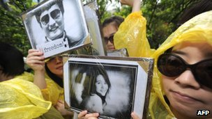 Taiwanese human rights activists display placards of blind Chinese dissident Chen Guangcheng (L) and his supporter He Peirong (R) during a protest outside the US institute in Taipei on May 4, 2012.