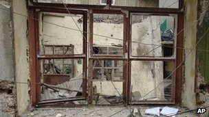 This image provided by the Local Coordination Committees activist network shows alleged damage to a building in Homs after shelling
