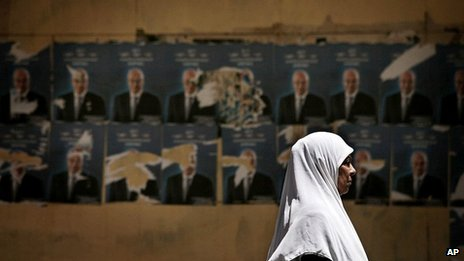 Woman walks past posters of Egyptian presidential candidate in Cairo (May 2012)