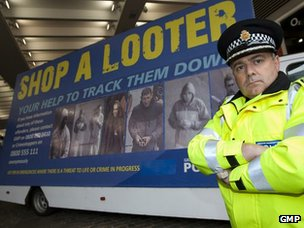 "Officer with Greater Manchester Police's ""Shop a Looter"" billboard"