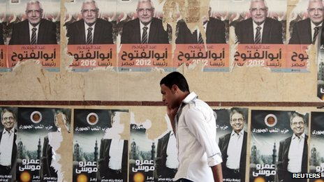 An Egyptian walks past election campaign posters of Amr Moussa and Abdel Moneim Abol Fotouh in Cairo.