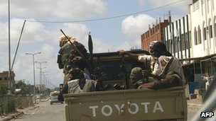 Yemeni militants, suspected of being members of Al-Qaeda patrol on a pick up in the restive southern city of Zinjibar in Yemen on 28 April 2012
