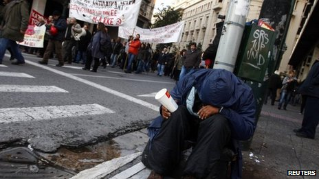A man begs on a street during a demonstration in Athens February 12, 2012.