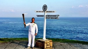 Ben Ainslie proudly holds aloft the torch at Land's End