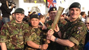 Sgt Robin Parker, Sgt Major Tim Rowe, Officer Cadet Andy Banfield, and Staff Sgt Paul Bushill hold Olympic torch