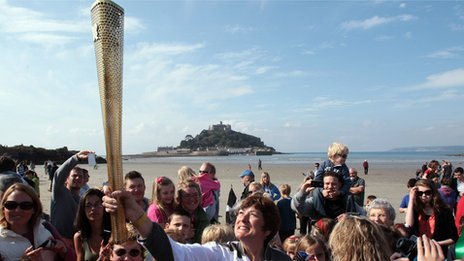 Sarah Blight holds the torch aloft near St Michael's Mount