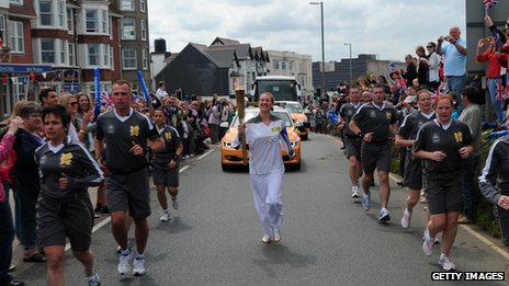An Olympic torchbearer running through the streets of Newquay