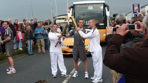 Mark Ormrod (right) taking on the flame from Adam Tofield in Plymouth