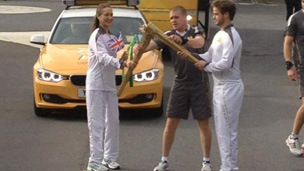 Gorgs Geikie passing the flame to Martin Morgan in Okehampton