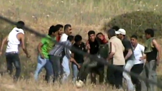 A Palestinian man being carried by other villagers after being shot