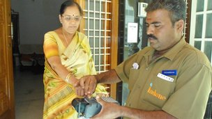 Woman in Mysore having fingerprint checked by gas man for ID number in pilot project