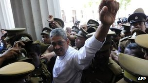 Sri Lanka&#039;s former army chief, Sarath Fonseka (C) waves to supporters as he arrives at the Colombo High Court in Colombo on November 18, 2011