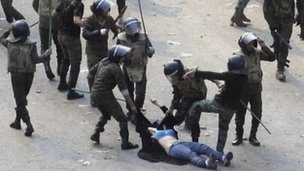 A woman being beaten by security forces in Tahrir Square, Cairo, December 2011.