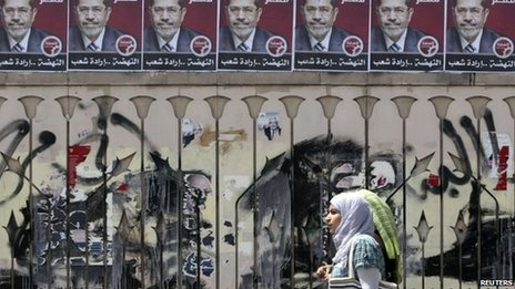 "Women walk under campaign election posters for Mohammed Mursi, the head of the Muslim Brotherhood""s political party in Cairo, April 2011"