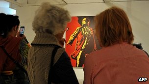 "Women look at the painting ""The Spear"" by Brett Murray at the Goodman Gallery in Johannesburg on May 18, 2012"